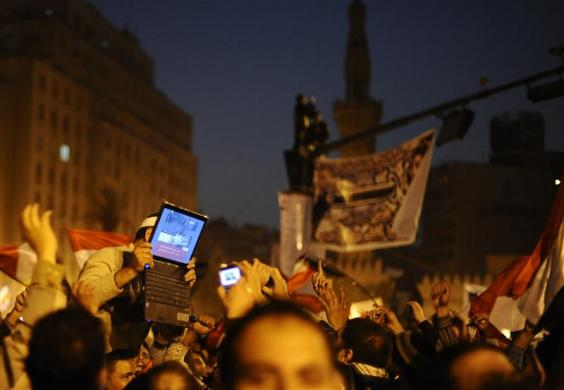 An opposition supporter holds up a laptop showing images of celebrations in Cairo's Tahrir Square, after Egypt's President Hosni Mubarak resigned